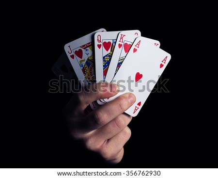 man hand shows royal flush playing card combination close-up on a black background - stock photo