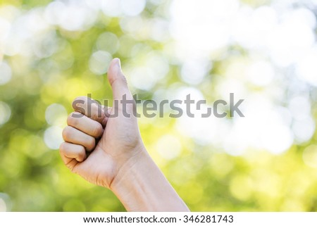 Man hand sign on green and yellow bokeh from tree background.