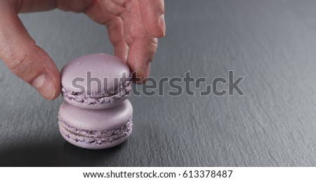 man hand stacking lavender macarons on slate board, 4k photo