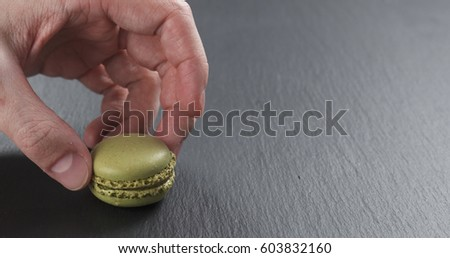 man hand stacking pistachio macarons on slate board, 4k photo