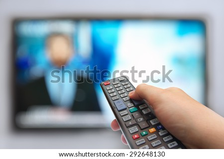 Man hand switches TV channels. Remote control in hand and TV. News in prime-time - stock photo