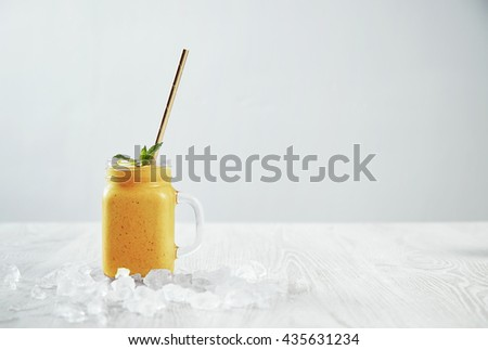 Man hand takes transparent rustic jar with tasty healthly freshly made yellow smoothie from mango, pineapple, banana and passion fruit. Melted ice around isolated on white table Easy to repaint - stock photo