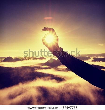 Man hand touch Sun. Misty daybreak in a beautiful hills. Peaks of hills are sticking out from foggy background, the fog is red and orange due to Sun rays.  - stock photo