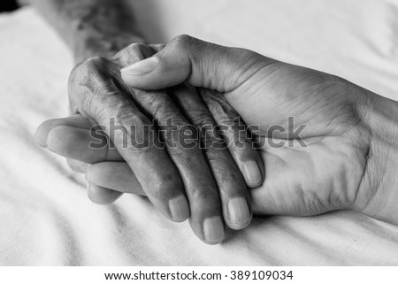 man hand touches and holds an old man wrinkled hands in clinic,black and white tone