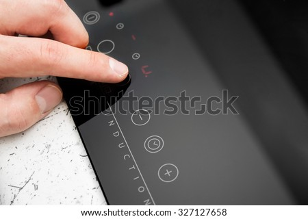 Man hand turns on modern induction cooker. - stock photo
