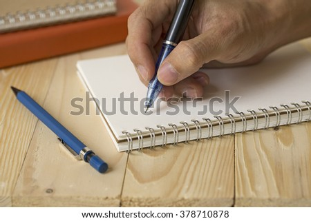 Man hand using pen pointing on notepaper book close up on wood vintage office table - stock photo