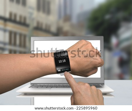 man hand wearing black glass smartwatch with bent interface on laptop and street background