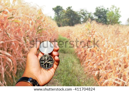 Man hand with a black and silver compass in of corn on the field blur. - stock photo