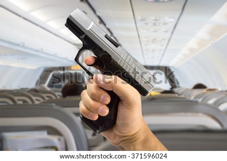 man hand with a gun into the plane - stock photo