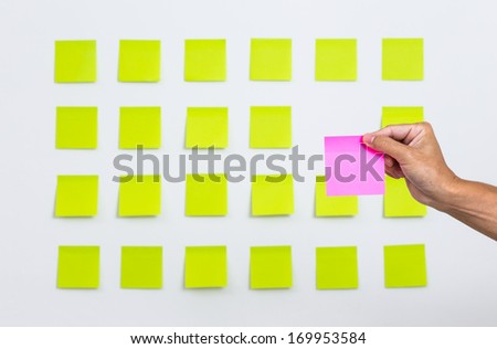 Man hand with adhesive paper note and stick on the wall