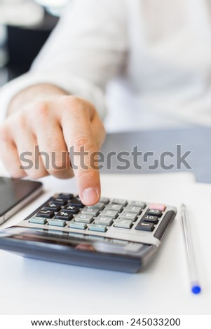 Man hand with calculator at workplace office.