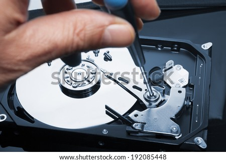 Man hand with screwdriver fixing or repairing hard drive or hard disc  - stock photo