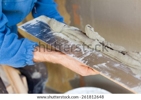 Man hand with trowel plastering a wall - stock photo