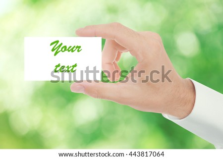 Man hand with white blank card on abstract green nature background - stock photo