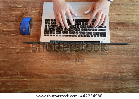 man hand working on laptop on wooden table - stock photo