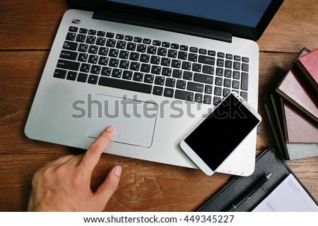 man hand working on phone and laptop on wooden table with relaxing feeling, man working on his laptop in a coffee shop, businessman hand busy using laptop at office desk,nice responsibility lifestyle