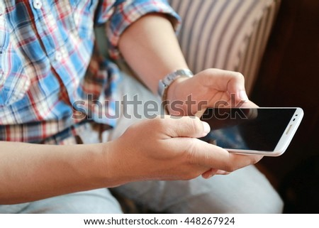 man hand working on phone on sofa with relaxing feeling, man working on his phone in a coffee shop, businessman hand busy using smartphone at office desk,nice responsibility lifestyle  - stock photo
