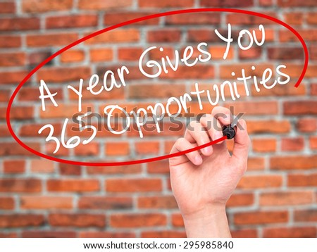 Man Hand writing A year Gives You 365 Opportunities with black marker on visual screen. Isolated on bricks. Business, technology, internet concept. Stock Photo - stock photo
