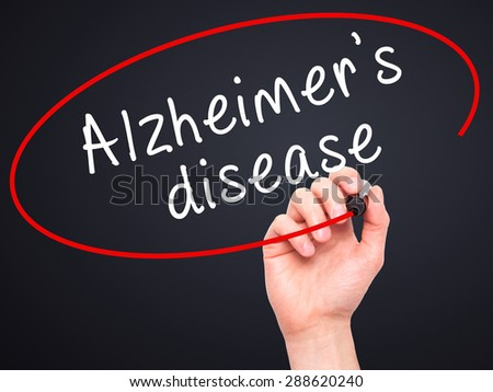 Man Hand writing Alzheimer's disease with black marker on visual screen. Isolated on black. Business, technology, internet concept. Stock Image