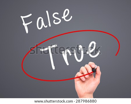 Man Hand writing an choosing True instead of False with black marker on visual screen. Isolated on grey. Business, technology, internet concept. Stock Image - stock photo
