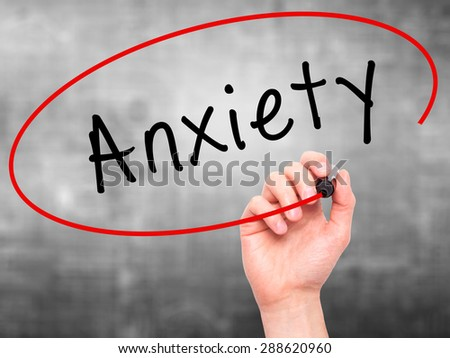 Man Hand writing Anxiety with black marker on visual screen. Isolated on grey. Business, technology, internet concept. Stock Image - stock photo