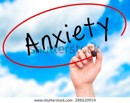 Man Hand writing Anxiety with black marker on visual screen. Isolated on sky. Business, technology, internet concept. Stock Image - stock photo