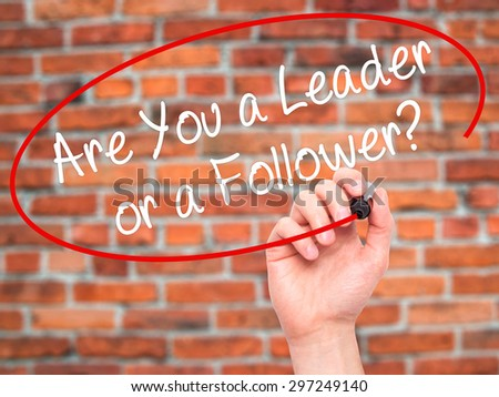 Man Hand writing Are You a Leader or a Follower? with black marker on visual screen. Isolated on bricks. Business, technology, internet concept. Stock Photo - stock photo