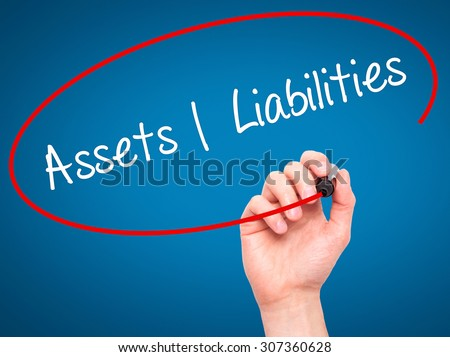 Man Hand writing Assets Liabilities with black marker on visual screen. Isolated on blue. Business, technology, internet concept. Stock Photo - stock photo