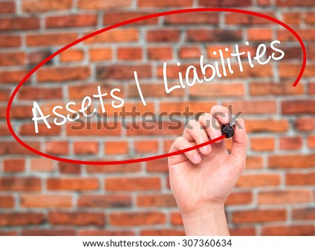 Man Hand writing Assets Liabilities with black marker on visual screen. Isolated on bricks. Business, technology, internet concept. Stock Photo - stock photo