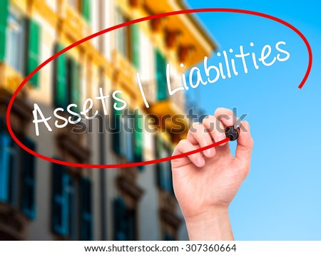 Man Hand writing Assets Liabilities with black marker on visual screen. Isolated on city. Business, technology, internet concept. Stock Photo - stock photo