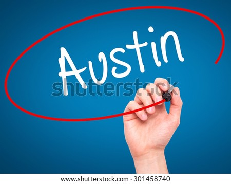 Man Hand writing Austin  with black marker on visual screen. Isolated on blue. Business, technology, internet concept. Stock Photo - stock photo