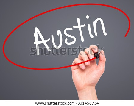 Man Hand writing Austin  with black marker on visual screen. Isolated on grey. Business, technology, internet concept. Stock Photo - stock photo