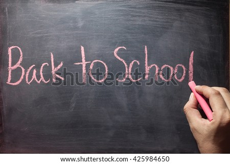 man hand writing back to school on blackboard.Back to school blackboard  concept - stock photo