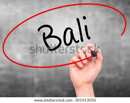 Man Hand writing Bali  with black marker on visual screen. Isolated on grey. Business, technology, internet concept. Stock Photo