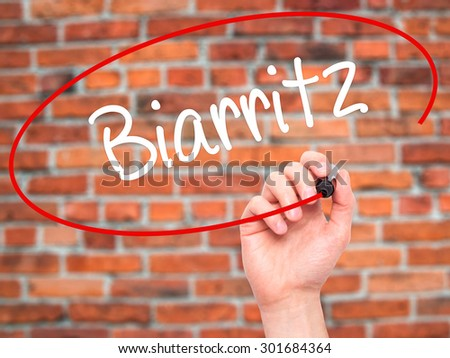 Man Hand writing Biarritz  with black marker on visual screen. Isolated on bricks. Business, technology, internet concept. Stock Photo - stock photo