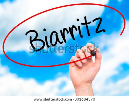Man Hand writing Biarritz  with black marker on visual screen. Isolated on sky. Business, technology, internet concept. Stock Photo - stock photo