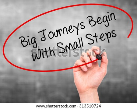 Man Hand writing Big Journeys Begin With Small Steps  with black marker on visual screen. Isolated on grey. Business, technology, internet concept. Stock Photo