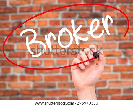 Man Hand writing Broker with black marker on visual screen. Isolated on bricks. Business, technology, internet concept. Stock Photo - stock photo