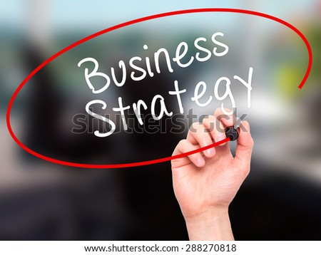 Man Hand writing Business Strategy with black marker on visual screen. Isolated on office. Business, technology, internet concept. Stock Image - stock photo