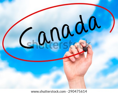 Man Hand writing Canada with black marker on visual screen. Isolated on sky. Life, technology, internet concept. Stock Image - stock photo