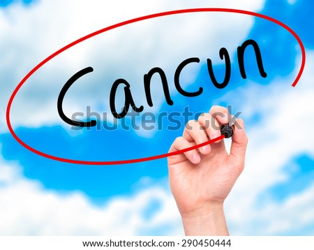 Man Hand writing Cancun with black marker on visual screen. Isolated on sky. Travel, technology, internet concept. Stock Image - stock photo