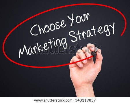 Man Hand writing Choose Your Marketing Strategy with black marker on visual screen. Isolated on black. Business, technology, internet concept. Stock Photo
