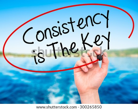 Man Hand writing Consistency is The Key with black marker on visual screen. Isolated on nature. Business, technology, internet concept. Stock Photo - stock photo