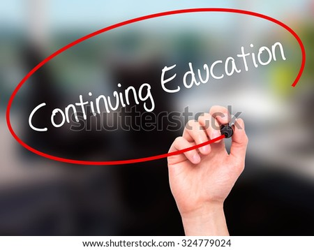 Man Hand writing Continuing Education with black marker on visual screen. Isolated on office. Business, technology, internet concept. Stock Photo - stock photo