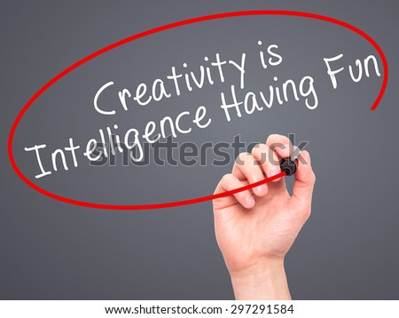 Man Hand writing Creativity is Intelligence Having Fun with black marker on visual screen. Isolated on grey. Business, technology, internet concept. Stock Photo - stock photo