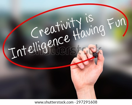 Man Hand writing Creativity is Intelligence Having Fun with black marker on visual screen. Isolated on office. Business, technology, internet concept. Stock Photo - stock photo