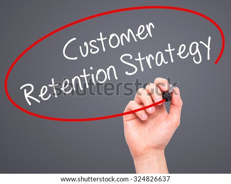 Man Hand writing Customer Retention Strategy with black marker on visual screen. Isolated on grey. Business, technology, internet concept. Stock Photo