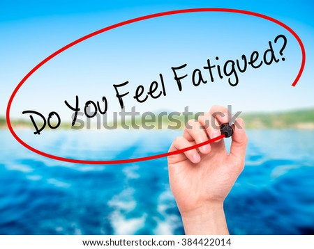 Man Hand writing Do You Feel Fatigued? with black marker on visual screen. Isolated on background. Business, technology, internet concept. Stock Photo - stock photo