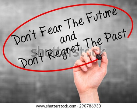 Man Hand writing Don't Fear The Future and Don't Regret The Past with black marker on visual screen. Isolated on grey. Life, technology, internet concept. Stock Image - stock photo
