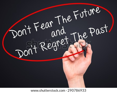 Man Hand writing Don't Fear The Future and Don't Regret The Past with black marker on visual screen. Isolated on black. Life, technology, internet concept. Stock Image